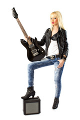 Beautiful woman in blue jeans posing with black electric guitar