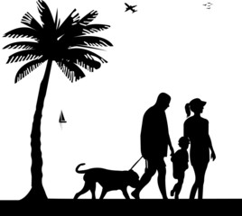 Family walking on beach with dog between the palms silhouette