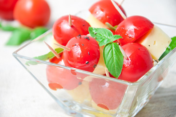 Tomato and  cheese slices decorated with basil leaves