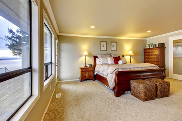 Master bedroom wtih beige walls and wood bed.