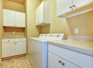 Laundry room with white cabinets and yellow walls.