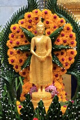 golden image of Buddha with flowers