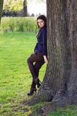 Beautiful young girl near tree