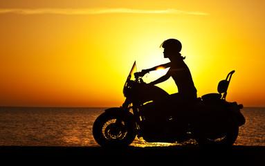 Wall Mural - Woman biker over sunset
