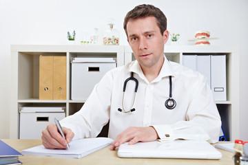 Arzt macht Notizen in seiner Praxis