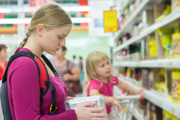 Mother and daughter shopping in tea and coffee section in superm