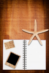 Star fish and notebook on the wood texture.