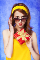 American redhead girl in sunglasses with gift.
