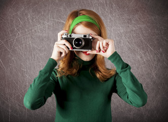 American redhead girl with camera.