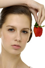 Close up young woman holding strawberry