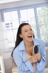 Happy woman laughing with hairbrush in hand