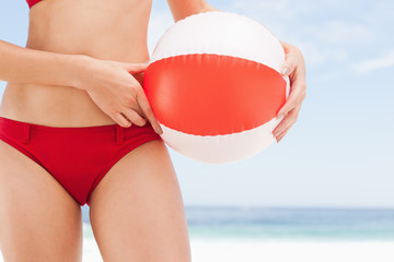Beach ball being held against a womans hip