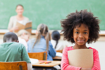 Smiling girl standing in classroom