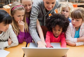 Teacher explaining laptop to students