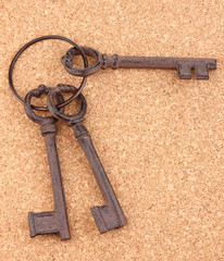 a bunch of antique keys on cork background