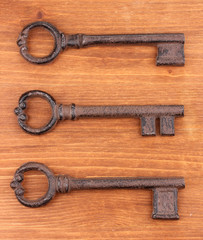 Three antique keys on wooden background