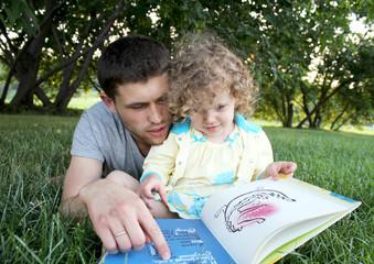 Счастливые папа и дочь в парке читают книгу