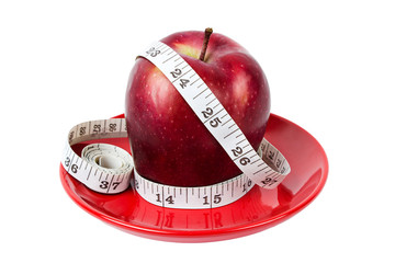Dieting concept Red apple with measuring tape on red plate