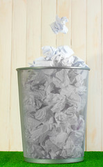metal trash bin from paper on grass on wooden background