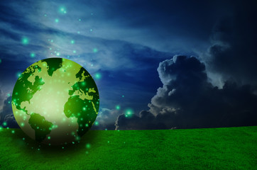 Green field and dark cloud with an earth globe laying in the gra