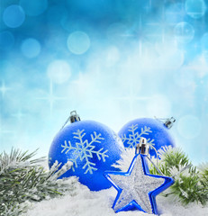 Christmas branch of tree blue baubles and snow background