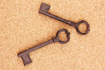 Two antique keys on cork background