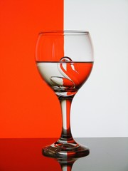 Glass with swan figure in it on red and white background