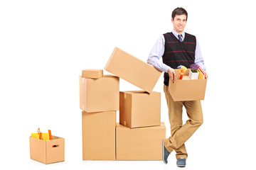 Full length portrait of a smiling male holding a box