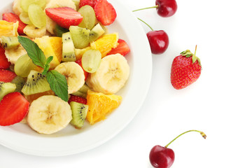 Fresh fruits salad on plate and berries isolated on white