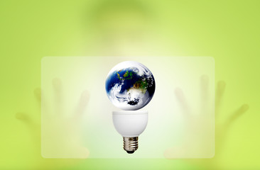 Man behind the green screen with bulb for green eco concept