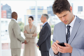 Young serious manager using his cell phone to send a text