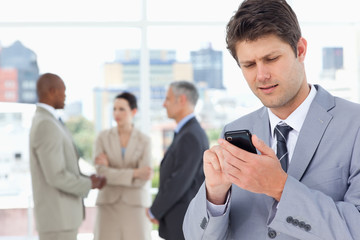 Young manager sending a text with his mobile phone in a concentr