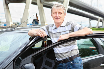 Happy mature driver with car key standing near own land vehicle