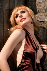 Beautiful blonde girl in evening dress, posing against a stone w