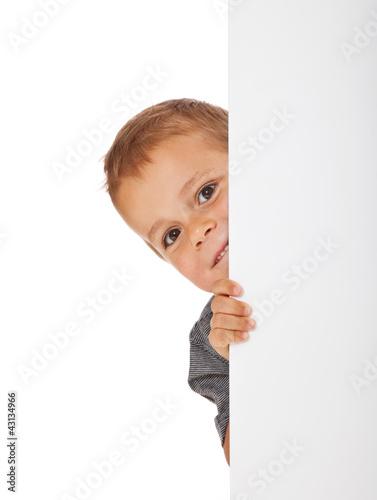 kleiner junge schaut neugierig hinter wei er wand hervor. Black Bedroom Furniture Sets. Home Design Ideas