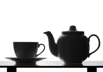 Teapot and cup on table. Silhouette
