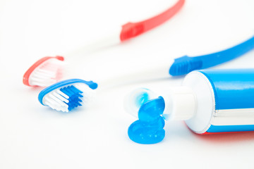 Two toothbrushes next to a tube of toothpaste