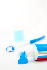 Blue toothbrush next to a tube of toothpaste