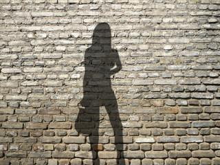 ombre de prostituée sur mur de briques
