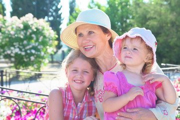 Grandma and her two granddaughters have a rest in the park