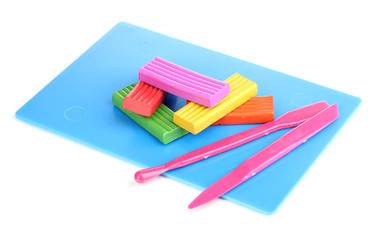 Children bright plasticine on desk with stacks isolated on