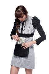 A young girl pulls dollars out of the bag. On a white background