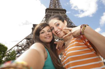 2 jeunes filles se prenant en photo devant la Tour Eiffel