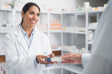 Smiling pharmacist giving a box to a doctor