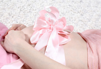 stomach of the pregnant girl and pink bow