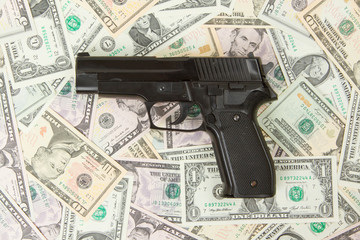 Black gun isolated on a heap of money