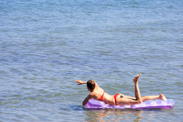 Beautiful girl swimming on air-mattress
