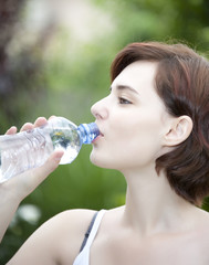 young girl drinking natural water