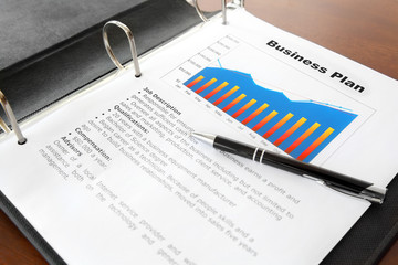 Business Plan with Pen in the Binder on the Table