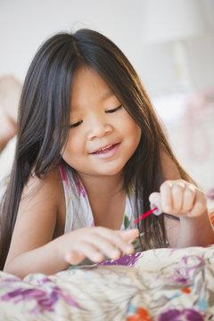 Korean girl putting on fingernail polish